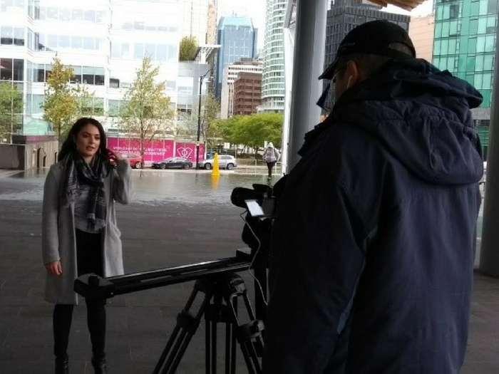Cesar stands behind the video camera in a black windbreaker, filming a beautiful woman with dark hair in front of a glass walled corporate building